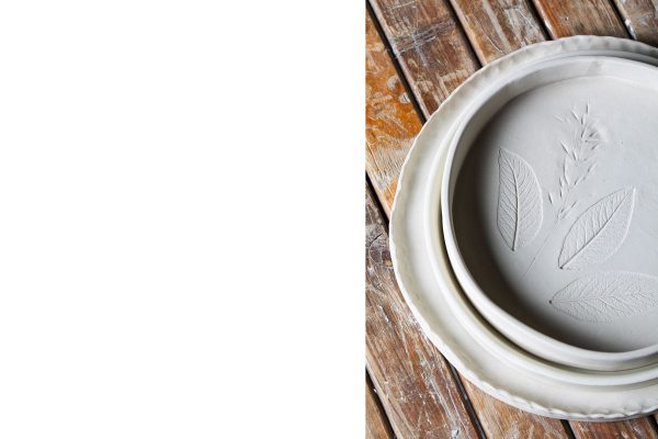 dettaglio di tre piatti di ceramica stampati con le foglie su un tavolo di legno - artigianale - Federica Ramacciotti