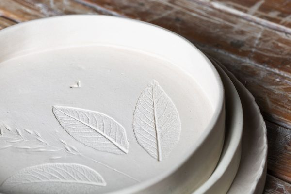 detail of three ceramic plates printed with nature on a wooden table - handmade - Federica Ramacciotti