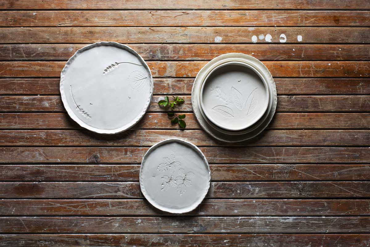 handmande ceramic plates printed with nature on a wooden table - Federica Ramacciotti