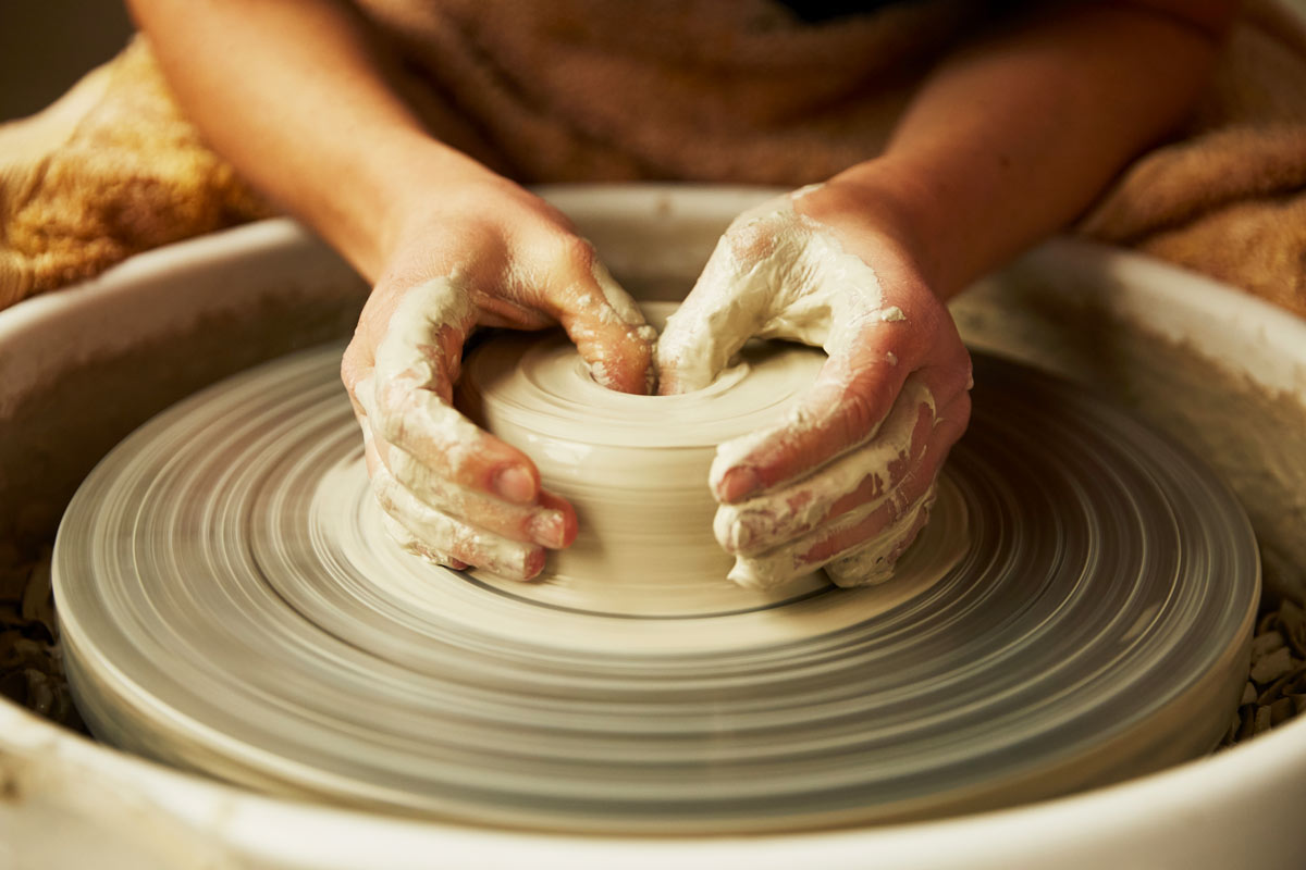 hands working clay on a ceramic wheel - Federica Ramacciotti