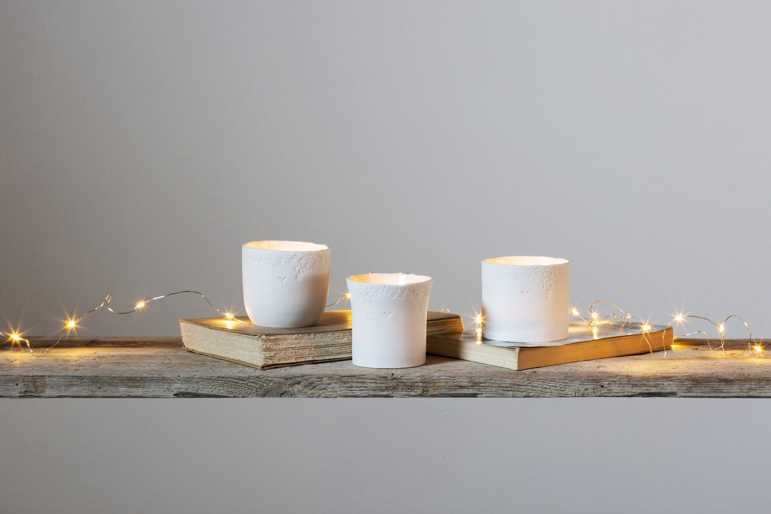 three white textured porcelain candle holders suspended on a shelf with books and lights - handmade - Federica Ramacciotti