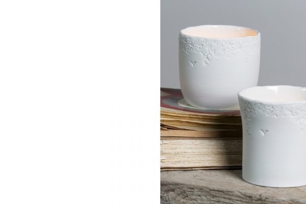 detail of two white textured porcelain candle holders resting on old books - handmade - Federica Ramacciotti