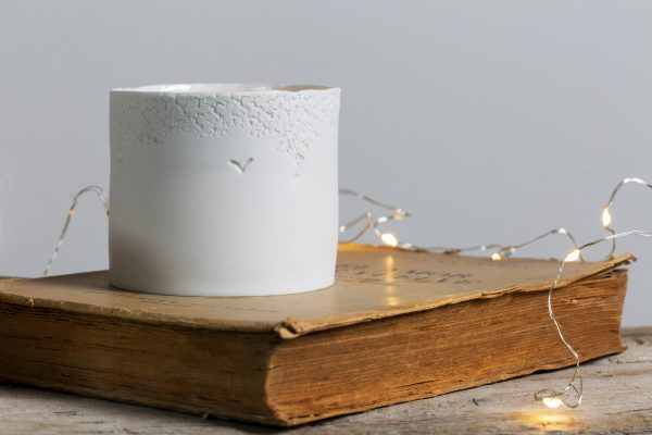 a white textured porcelain candle holder resting on an old book - handmade - Federica Ramacciotti