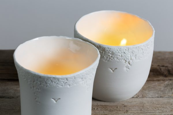detail of two white porcelain candle holders with texture and light on - handmade - Federica Ramacciotti