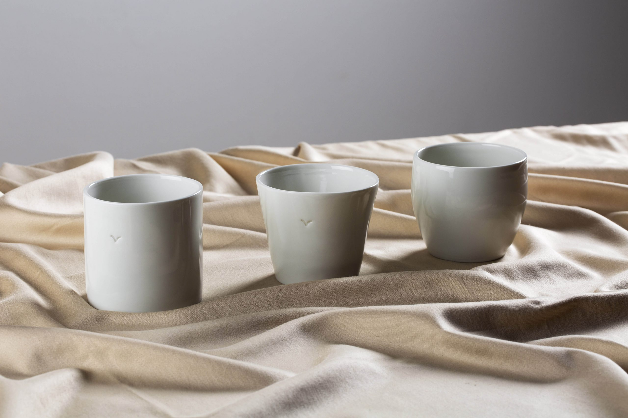three handmande white porcelain cups in a row on a fabric - Federica Ramacciotti