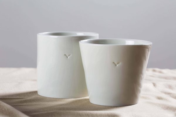 two white porcelain mugs made by hand on some fabric - Federica Ramacciotti