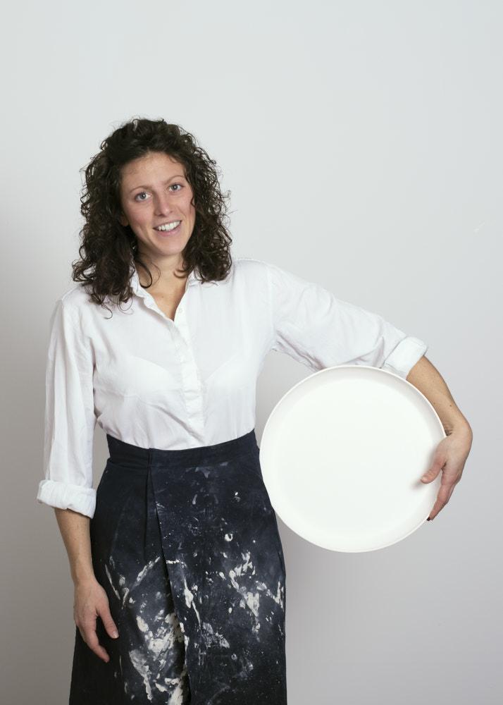 una artigiana ceramista che tiene un piatto nelle sue mani - Federica Ramacciotti