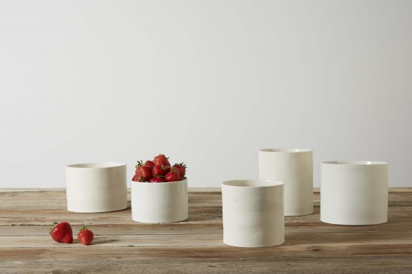 five white porcelain vases on a wooden table with some strawberries - handmade - Federica Ramacciotti - handmade - Federica Ramacciotti