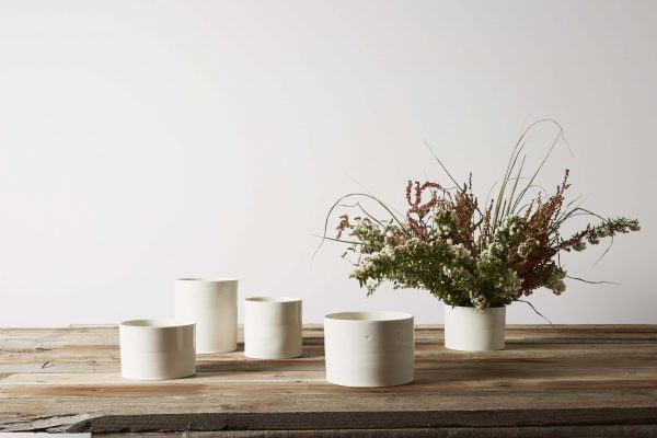 five white porcelain vases on a wooden table with some flowers - handmade - Federica Ramacciotti