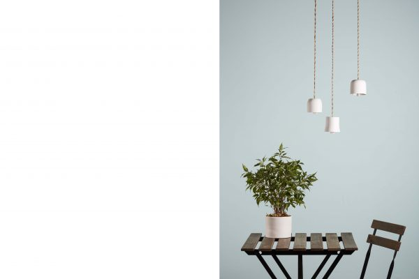 three white porcelain bells suspended on an outdoor table with a plant - handmade - Federica Ramacciotti