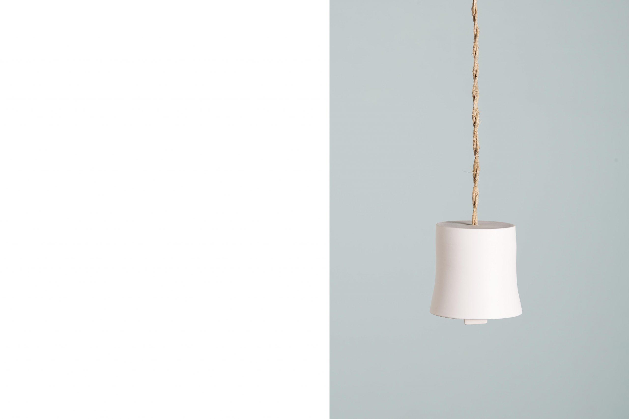 una campanella in porcellana bianca sospesa con una corda intrecciata - artigianale - Federica Ramacciotti