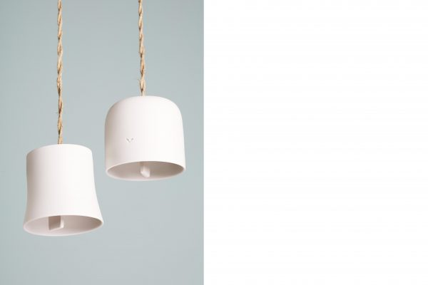 detail of two white porcelain bells suspended by a rolled-up rope - handmade - Federica Ramacciotti