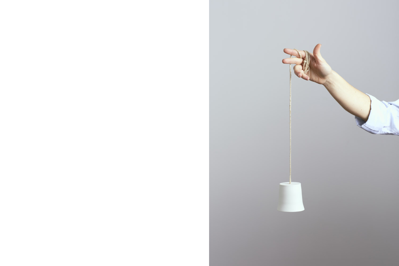 la mano di un artigiana ceramista che tiene una campanella un porcellana bianca - artigianale - Federica Ramacciotti