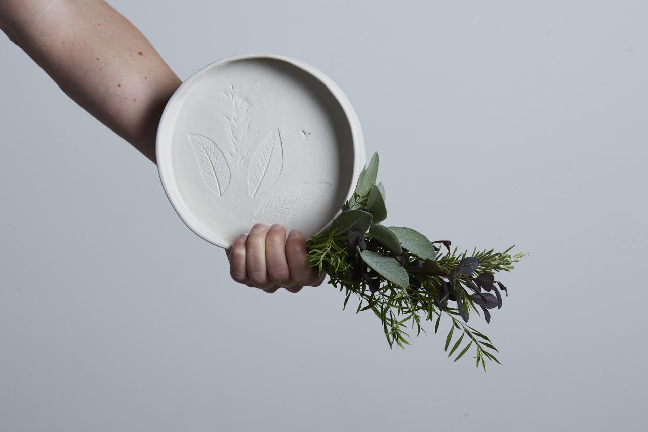 un piatto in ceramica con delle impronte e un mazzolino di vegetazione tenuto dalla mano dell'artigiana - fatto a mano - Federica Ramacciotti